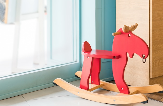 Red rocking horse toy for kid in home living room, cheerful riding stuff child furniture background