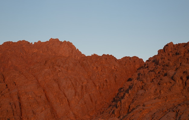 Red rocky mountains against the blue sky