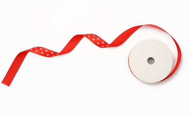 Red roll of silk green ribbon, wrapping decor, white background, top view