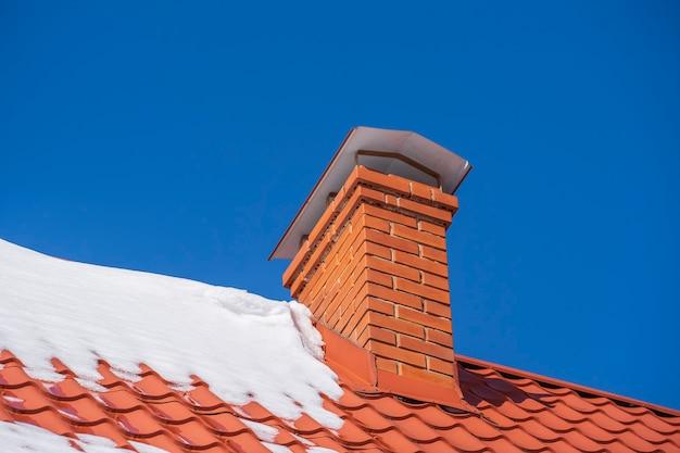 단독 주택의 빨간 지붕과 굴뚝, 겨울의 푸른 하늘에 눈, 클로즈업 프리미엄 사진
