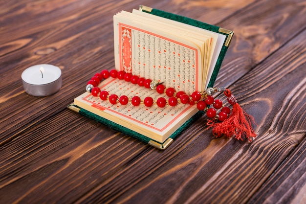 Red rosary beads inside an open islamic holy kuran book with lighted candle on wooden surface