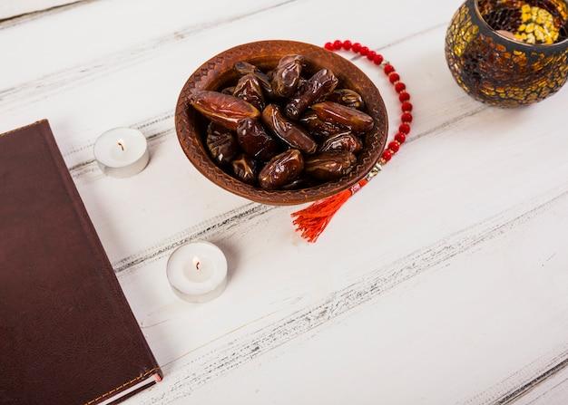 ジューシーな日付と白い木製のテーブルの上のろうそくのボウルと赤いロザリオビーズ