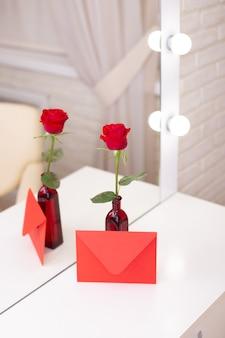 美容院のテーブルの上に、赤いバラとコピースペースのある封筒。