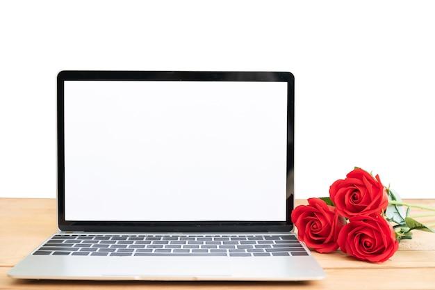 赤いバラと白い背景の上のラップトップのモックアップ、バレンタインの概念