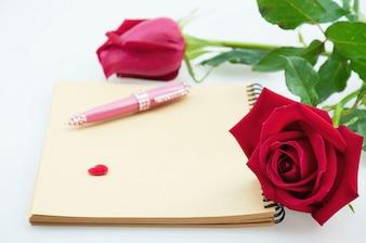 Красная роза и розовая ручка с блокнотом на белом фоне