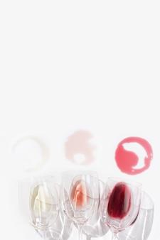 日光の下で赤、バラ、白ワインの上面図。白いテーブルの上のガラスの盛り合わせワイン。