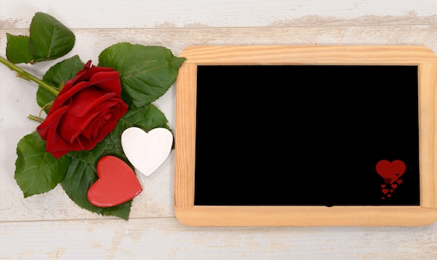 Red rose and black slate on a wood table