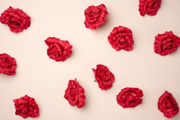 Red rose buds from textile on a beige background, top view