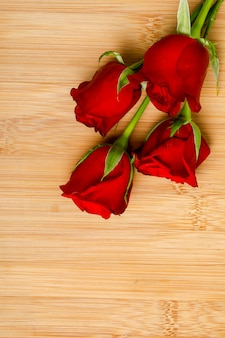 Red rose bunch and gift box on wooden board. valentine day concept