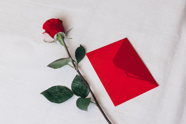 Red rose and envelope with copy space, laying on white bed.
