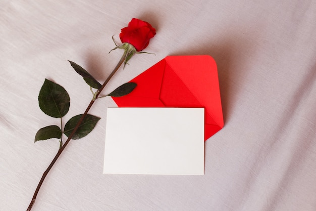Red rose and envelope with copy space on white bed background