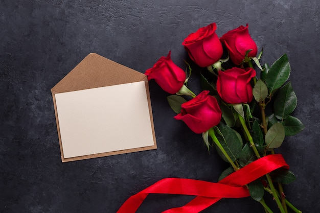 Red rose flowers bouquet and an envelope on black stone. valentine's day greeting card with copyspace