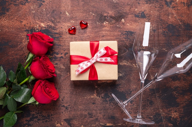 Red rose flowers bouquet, gift box and champagne glasses on wooden background