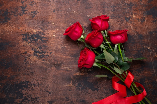 Red rose flowers bouquet on wooden background valentine's day greeting card