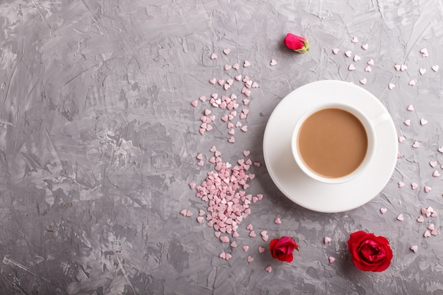 Red rose flowers and a cup of coffee on gray concrete