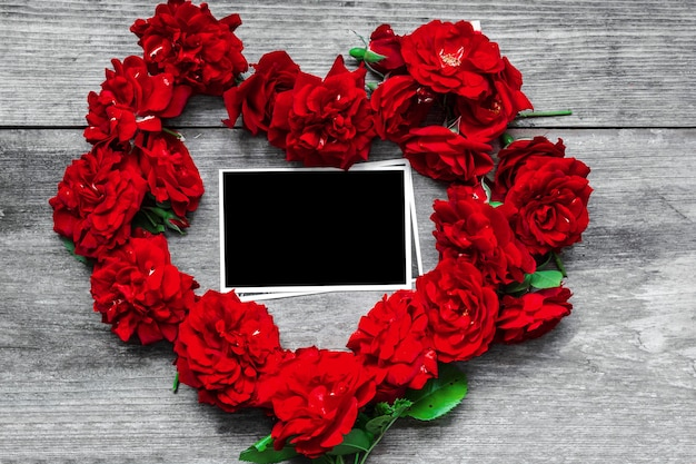 Red rose flowers heart shaped with blank photo frame on rustic wooden table