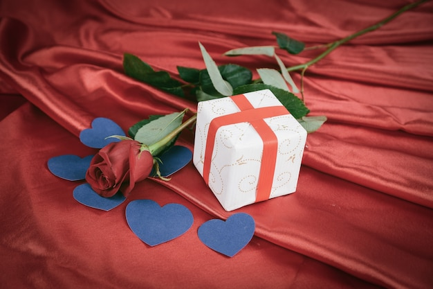 Red rose and gift box on red background. valentine's day