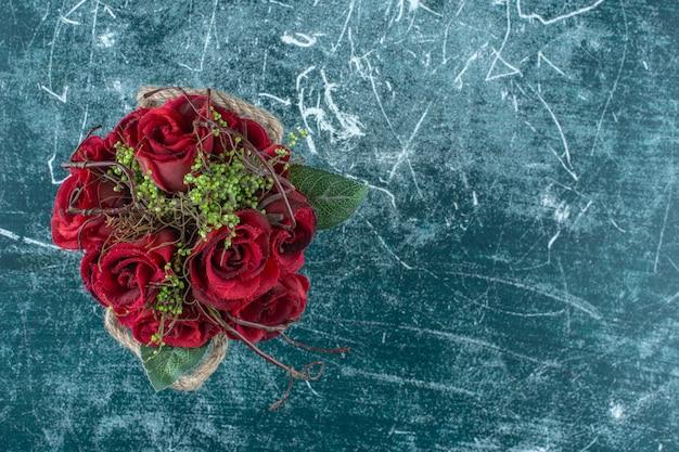 青い背景に、バケツの中で赤いバラ。