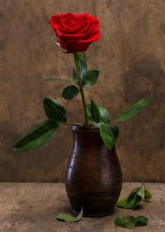 나무 배경에 꽃병에 빨간 장미