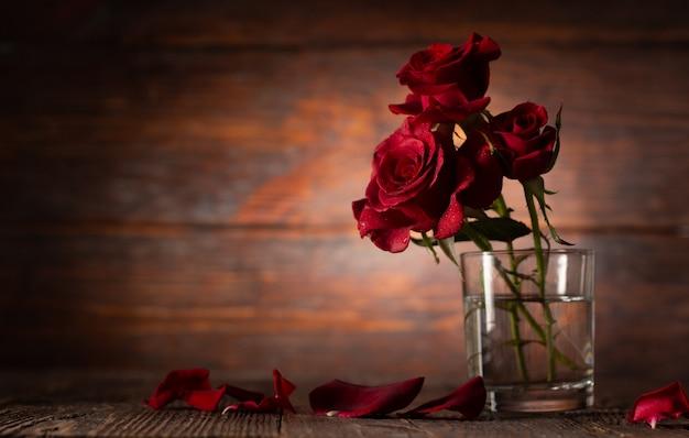 Красная роза в вазе на старом деревянном столе, винтажный стиль