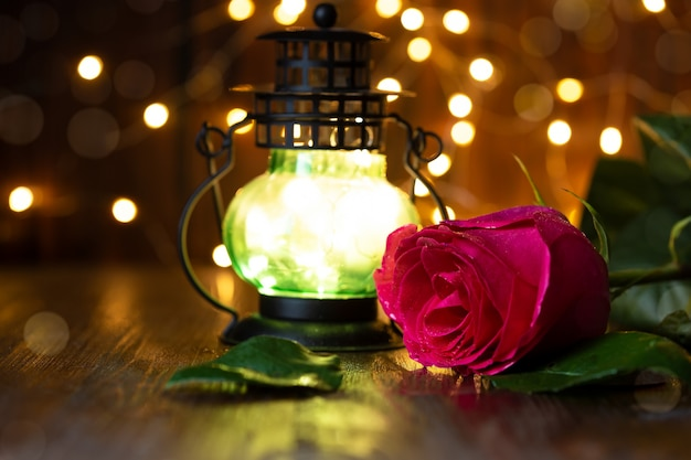 Red rose and lantern with lights on a wooden table.