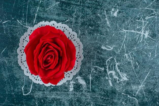 青い背景のコースターに赤いバラ。
