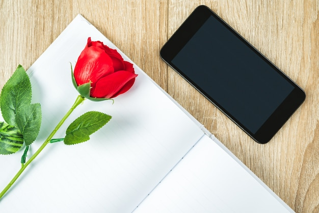 スマートフォンの横にある空白のノートブック日記に赤いバラ