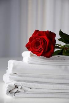 흰색 테이블에 흰색 줄무늬 침구에 빨간 장미. 발렌타인 데이 아침