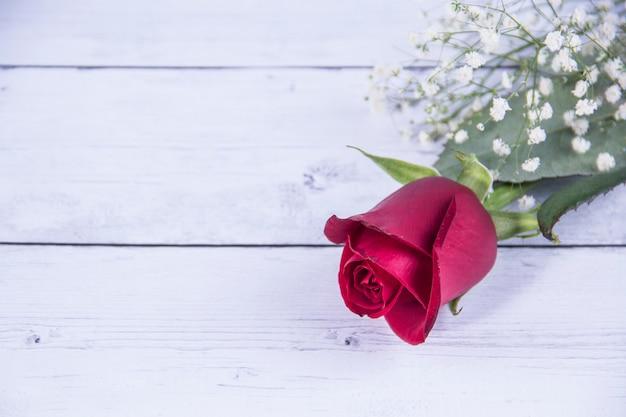 白い木製のテーブルに赤いバラ