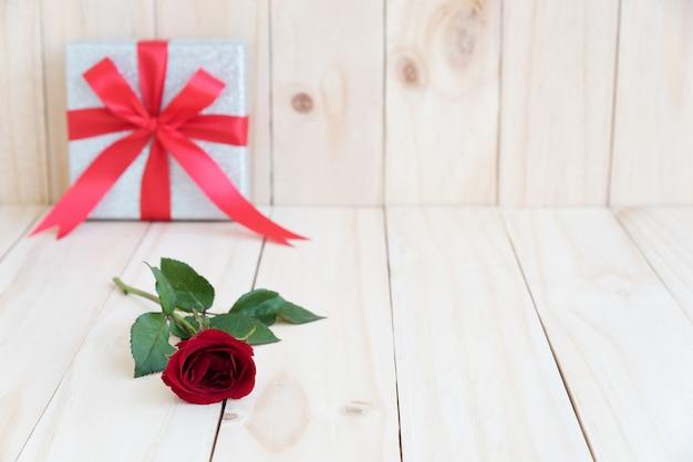 木製の背景に赤いバラ