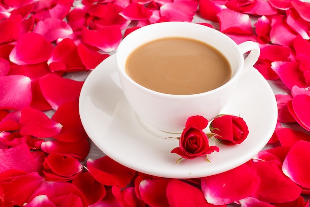 Red rose petals background and a cup of coffee.
