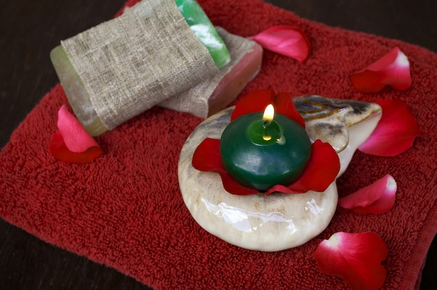 Red rose petals, candle, soap and towel
