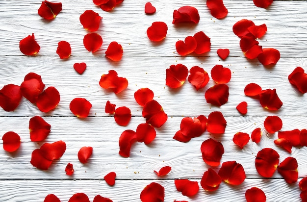 Red rose petals and small red wooden hearts on a white wooden background. top view. st. valentine's day background.