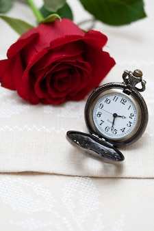 Red rose and pocket watch on napkin embroidered with cross