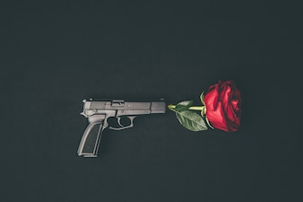 Red rose shooting from gun isolated on black