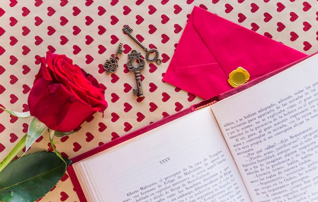 Red rose with book and envelope on table