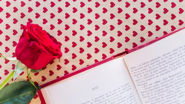 Red rose with book on table