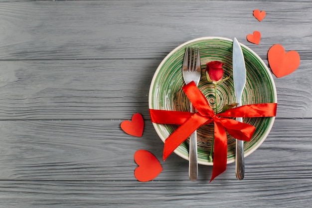 Red rose with cutlery on bowl