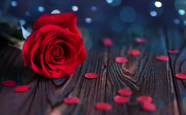 Красная роза с каплями росы на деревянном фоне с боке, крупным планом