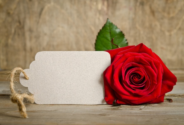 Red rose with empty tag for your text on wooden table