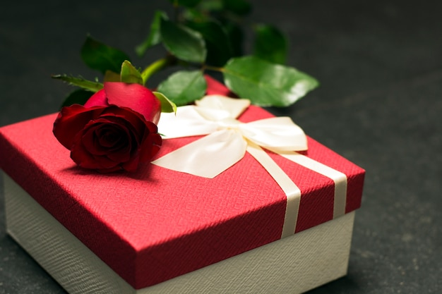 Red rose with gift box on dark background