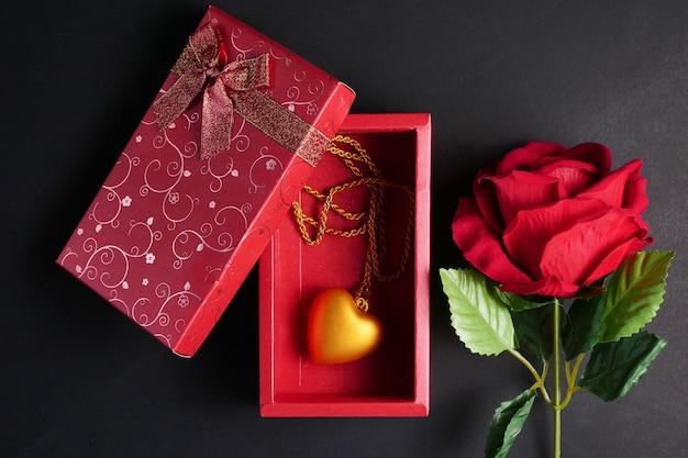 赤、黒の背景に赤のギフトボックスで金の心臓のネックレスとバラ。バレンタインデーのコンセプト。