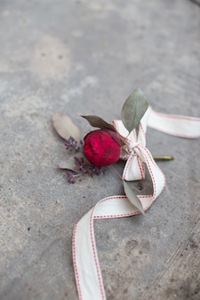 Red rose with ribbon on the concrete ground. high quality photo