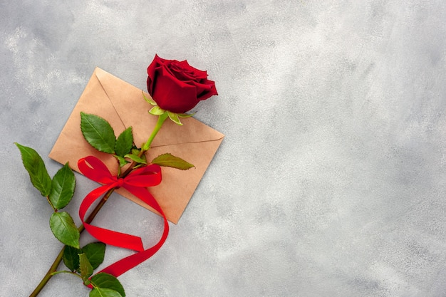 Red rose with a ribbon and love letter