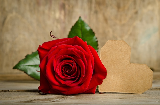 Red rose with valentine for text on wooden table