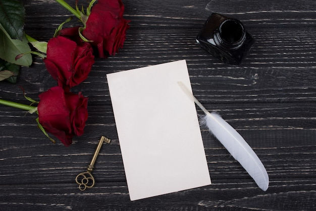 Красные розы, ключ, открытка, перо и чернильница