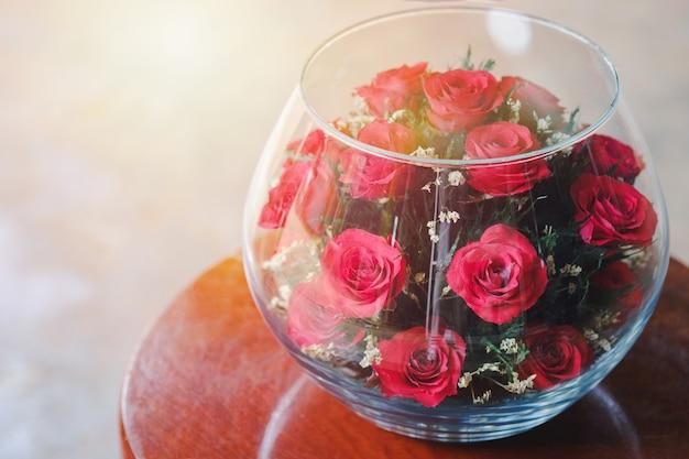 家の内部を飾るためにテーブルの上の大きなガラスの瓶に飾られた赤いバラ