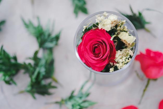 유리에 빨간 장미와 장식용 잎이 테이블에 아름답게 배열되어 있습니다