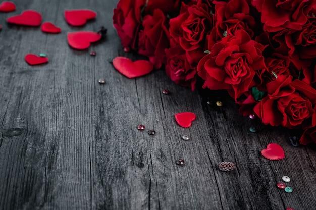 コピースペースのある暗い古い木製の赤いバラとハート