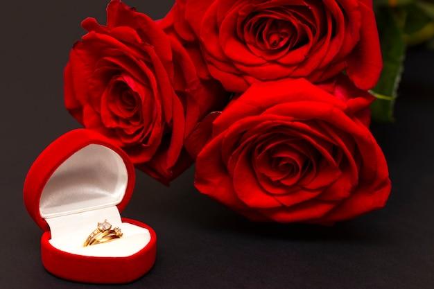 黒の背景に赤いバラとハート。バレンタインデーの背景